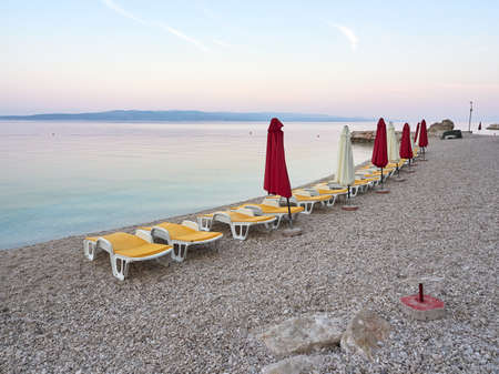 Empty sun loungers and umbrella on Ikovac beach in Baska Voda. A seaside resort waiting for tourists. A beautiful quiet morning on the Adriatic in a Croatian city