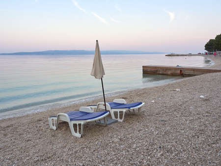 Empty sun loungers and umbrella on Podluka beach in Baska Voda. A seaside resort waiting for tourists. A beautiful quiet morning on the Adriatic in a Croatian city Stock fotó