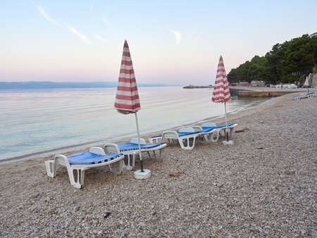 Sun beds and umbrellas on the Podluka beach in the seaside resort of Baska Voda. A beautiful quiet morning by the sea.