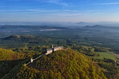 Bezdez castle and surrounding countryside with lake Machovo lake behind - aerial photo from ultralight plane in central Bohemian region in Czech Republic \ t