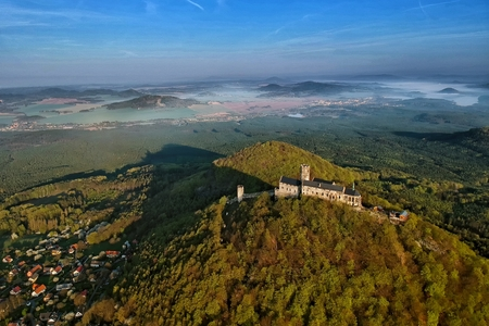Bezdez castle and surrounding countryside with Machovo lake lake behind - aerial photo from ultralight plane in central Bohemian region in Czech Republic \ t