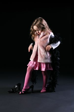 ni�os vistiendose: Cinco a�os cute poco ni�a vestirse para una fiesta. Estudio dispar� sobre fondo negro.  Foto de archivo