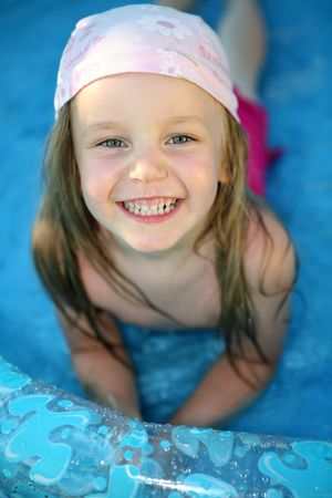 A nice view of a cute four-year old girl playing in the shallow water of a plastic inflatable wading pool. photo