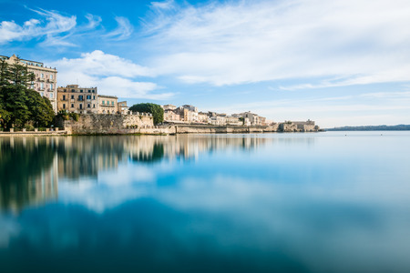 Coast of Ortigia island at city of Syracuse. Long exposure sea. Reflection in water. Landscape reflection in sea