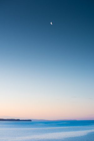 Moon over the Atlantic Ocean with purple sky and mountains in the background