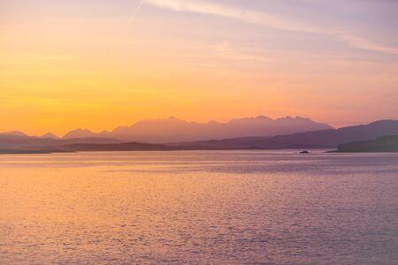 Isle of Skye Sunrise - golden sun glow on ocean, mountains and islands