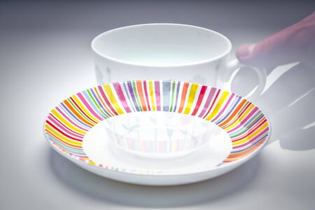 Vanishing hand holing a coffee cup and saucer - colourful and stylish afternoon tea set Banco de Imagens - 130732682