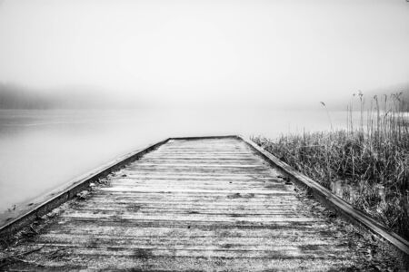 Misty lake in the middle of the forest and old wooden bridge Banco de Imagens - 130734104