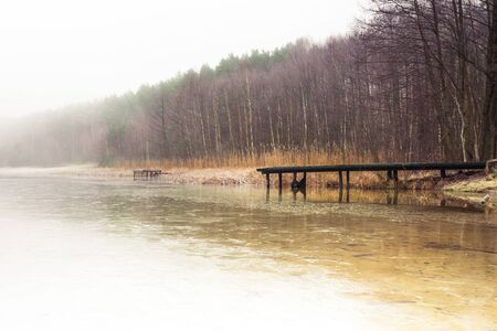 Misty lake in the middle of the forest and old wooden bridge Banco de Imagens - 130734131
