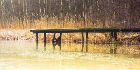 Misty lake in the middle of the forest and old wooden bridge Banco de Imagens - 130734132