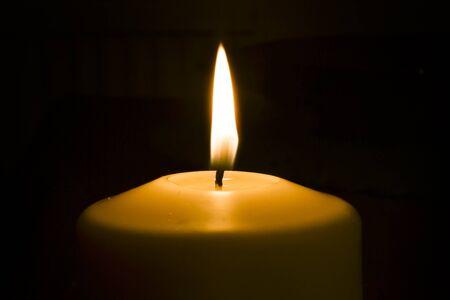 Fiamma di candela sullo sfondo scuro e spazio per il testo