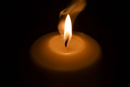 Candle flame in the dark background and space for text