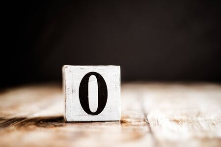 0 - Number 0 - Number Zero - White block with number on wooden table and dark background Фото со стока