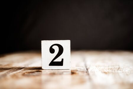 2 - Number 2 - Number Two - White block with number on wooden table and dark background