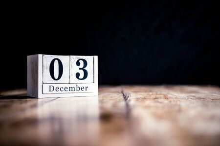 December 3rd, 3 December, Third of December - White block calendar on vintage table - Date on dark background Фото со стока