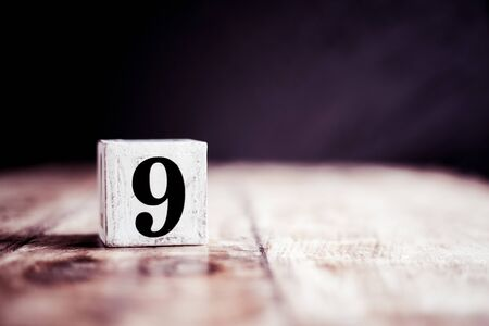 Number 9 isolated on dark background- 3D number nine isolated on vintage wooden table