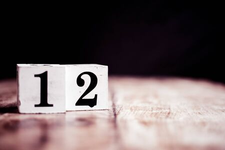 Number 12 isolated on dark background- 3D number twelve isolated on vintage wooden table