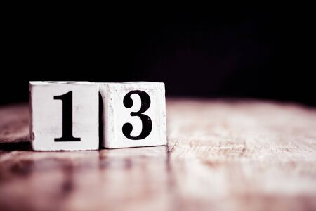Number 13 isolated on dark background- 3D number thirteen isolated on vintage wooden table