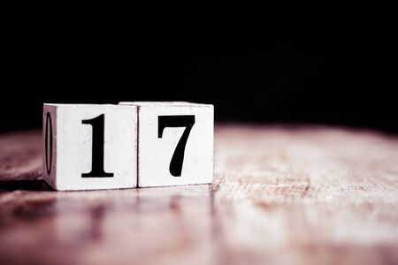 Number 17 isolated on dark background- 3D number seventeen isolated on vintage wooden table