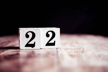 Number 22 isolated on dark background- 3D number twenty two isolated on vintage wooden table Banco de Imagens