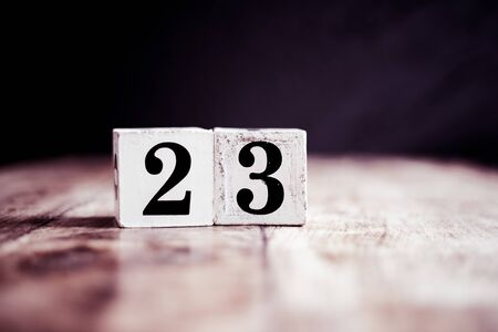 Number 23 isolated on dark background- 3D number twenty three isolated on vintage wooden table Banco de Imagens