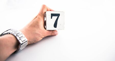 A hand holding digit number 7 (seven) on white background Banco de Imagens