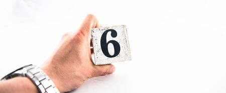 A hand holding digit number 6 (six) on white background Banco de Imagens