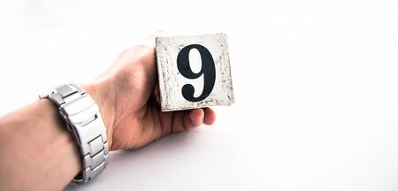 A hand holding digit number 9 (nine) on white background