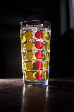 Tall colourfull glass filled with iced lemonade isolated on dark background Banco de Imagens