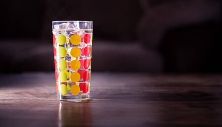 Tall glass with green, orange and red dots filled with ice cubes and lemonade isolated on dark background