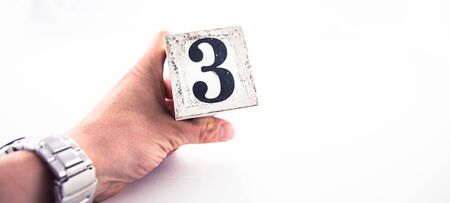 A hand holding digit number 3 (three) on white background
