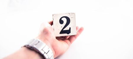 A hand holding digit number 2 (two) on white background