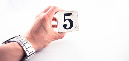 A hand holding digit number 5 (five) on white background