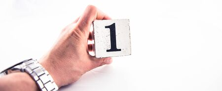 A hand holding digit number 1 (one) on white background Banco de Imagens