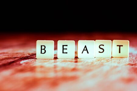 Beast word made of tiles on dark wooden background Banco de Imagens - 130873990