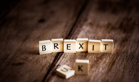 UK and Brexit word made of tiles on dark wooden background Banco de Imagens - 130873991