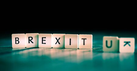 UK leaving EU - word made of tiles on dark wooden background