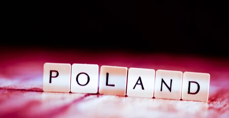 Poland word made of tiles on dark wooden background Banco de Imagens - 130873997