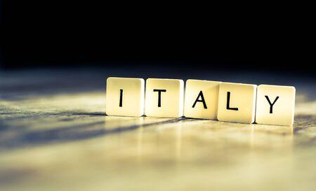 Italy word made of tiles on dark wooden background Banco de Imagens