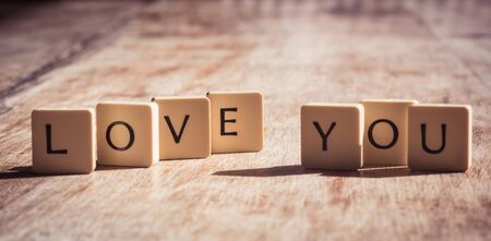 Love you word made of tiles on dark wooden background