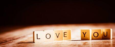 Love you word made of tiles on dark wooden background Banco de Imagens - 130874003