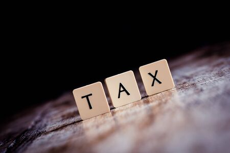 Tax word made of tiles on dark wooden background
