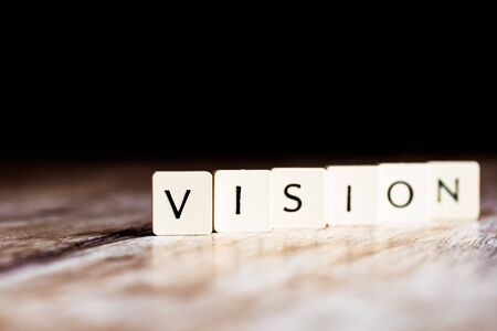 Vision word made of tiles on dark wooden background Banco de Imagens