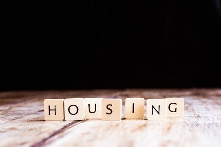 Housing word made of tiles on dark wooden background Banco de Imagens