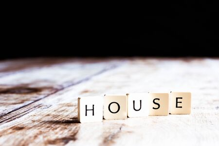 House word made of tiles on dark wooden background Banco de Imagens - 130874032