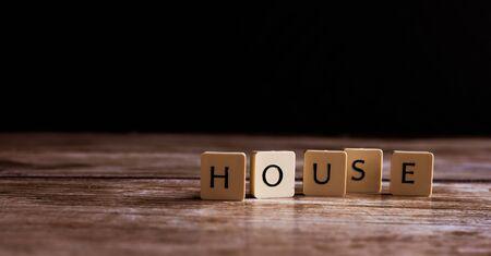 House word made of tiles on dark wooden background Banco de Imagens