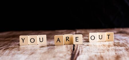 You are out word made of tiles on dark wooden background Banco de Imagens