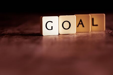 Goal word made of tiles on dark wooden background