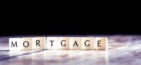 Mortgage word made of tiles on dark wooden background Banco de Imagens - 130874038
