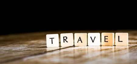 Travel word made of tiles on dark wooden background Banco de Imagens - 130874040
